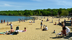 © Licensed to London News Pictures. 20/05/2020. LONDON, UK.  Members of the public take advantage of the easing of certain coronavirus pandemic lockdown restrictions to enjoy the sunshine and warm weather at the beach at Ruislip Lido in north west London.   The forecast is for temperatures to rise to 29C, the hottest day of the year so far.  Photo credit: Stephen Chung/LNP