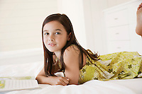 Girl reading story book lying on stomach on bed
