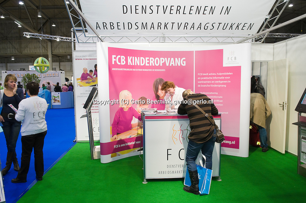 Nederland, Den Bosch, 20101105..KindVak, vakbeurs voor professionals in de kinderopvang, buitenschoolse opvang en brede scholen. In de Brabanthallen in Den Bosch..Stand van FCB Kinderopvang. Arbeidsmarktorganisatie van en voor werkgevers en werknemers. Roze achtergrond...Netherlands, Den Bosch, 20101105..KindVak, trade show for professionals in child care, after school care and community schools. In the Brabant Hallen in Den Bosch..Stand of FCB Childcare. Labour market Organisation, for employers and employees. Pink background.