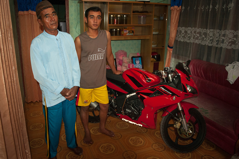 Darman (53 years) with his son Swanda (21 years) who was able to by himself a new motorcycle with the money he earned in the mine.  Bangka Island (Indonesia) is devastated by illegal tin mines. The demand for tin has increased due to its use in smart phones and tablets.<br /> <br /> Darman (53 ans) avec son fils Swanda (21 ans) qui a pu s'acheter une moto grosse cylindr&eacute;e gr&acirc;ce &agrave; l'argent de l'&eacute;tain. L'&icirc;le de Bangka (Indon&eacute;sie) est d&eacute;vast&eacute;e par des mines d'&eacute;tain sauvages. la demande de l'&eacute;tain a explos&eacute; &agrave; cause de son utilisation dans les smartphones et tablettes