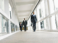 Businessmen walking down corridor (low angle view)