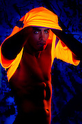 A young muscular man takes off a glowing shirt.Black light
