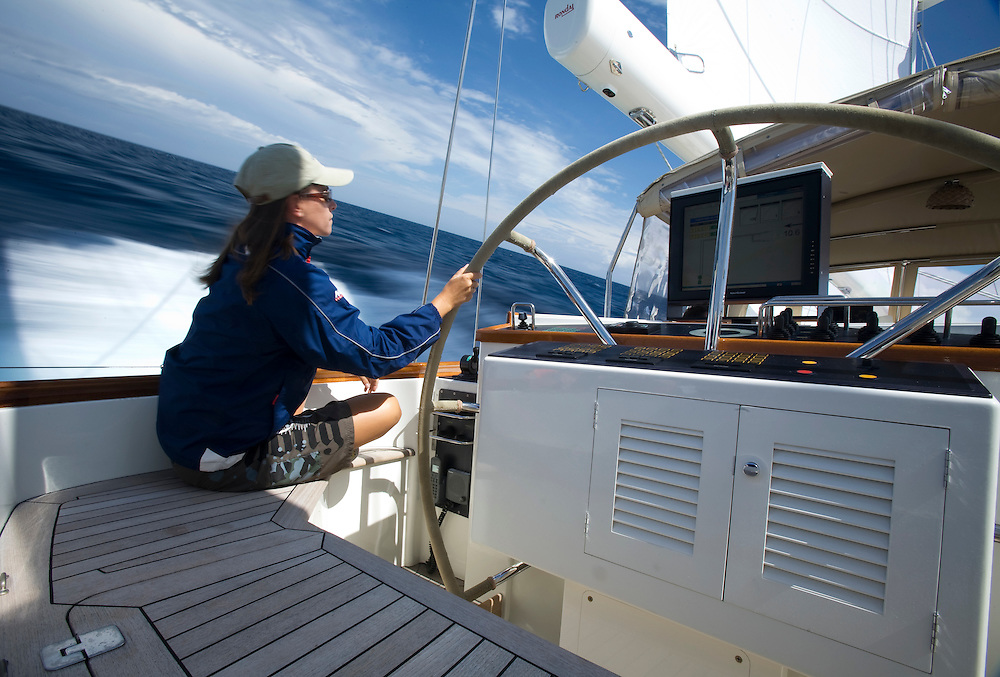 A crew member steers the sailing yacht Scheherazade as she sails across the Atlantic ocean.