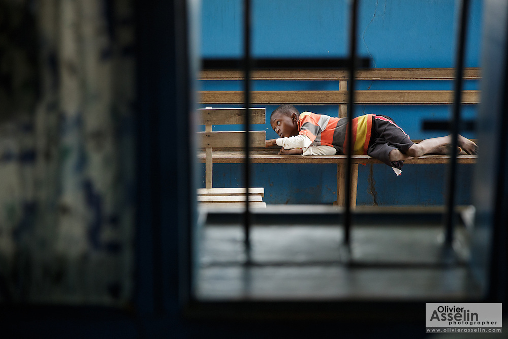 A boy lies on a benchm at the Libreville health center in Man, Cote d'Ivoire on Wednesday July 24, 2013.