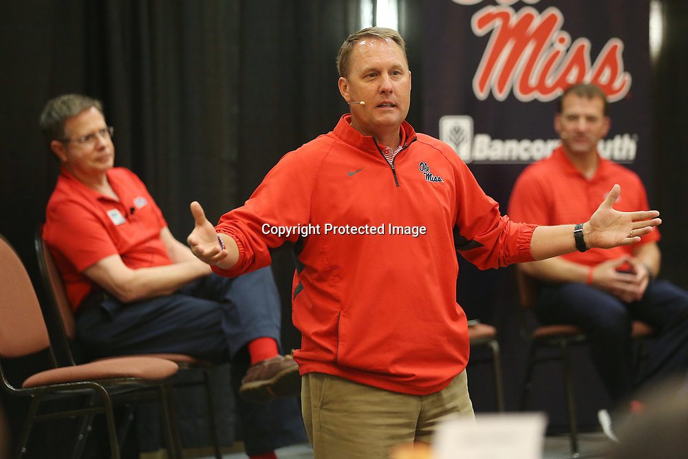 Ole Miss football head coach Hugh Freeze speaks to the alumni gathered Wednesday evening during the Rebel Roadshow as Chancellor Jeff Vitter, left, and Athletic Director Ross Bjork, right, sit nearby at the BancorpSouth Conference Center.