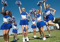 Group of Cheerleaders rising pom-poms jumping on football field