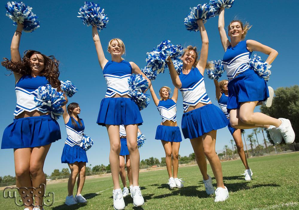 Group of Cheerleaders rising pom-poms jumping on football field