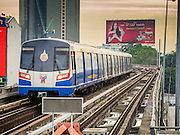 28 OCTOBER 2014 - BANGKOK, THAILAND: A Bangkok Skytrain pulls into the Saphan Taksin station. The Skytrain (called the BTS) system has a combined length of 36 kilometres and includes 34 stations, including Saphan Taksin. While there are two train tracks for most stretches of the Skytrain system, the portion on the Saphan Taksin Bridge spanning the Chao Phraya River has just one track due to limited space, causing a bottleneck when an outbound train and inbound train arrive at the bridge at the same time. The Bangkok Metropolitan Authority (BMA) had sought permission from the Department of Rural Roads to expand the Taksin Bridge in order to make way for an additional track, but the department had said it was not possible. The Saphan Taksin  station was originally supposed to be temporary and is one of the busiest on the system. It's a connecting station for the Chao Phraya River boats used by Thai commuters coming into the city from neighboring provinces and tourists who use the boats to go upriver into the old parts of Bangkok from the central business district. More than 4,000 commuters a day use the station. The BMA plans to build an elevated moving sidewalk to the river from Surasak BTS station about one kilometer away. Surasak is the nearest station to Saphan Taksin. The Skytrain system has a combined length of 36 kilometres and includes 34 stations, including Saphan Taksin.        PHOTO BY JACK KURTZ