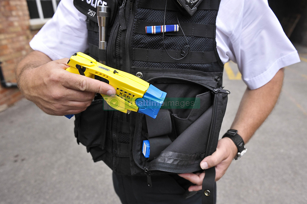 File photo dated 13/07/09 of an Avon and Somerset police officer holstering a Taser X26 during a training exercise. Britain's largest police force is to equip hundreds more officers with Tasers after a surge in violence and knife crime.
