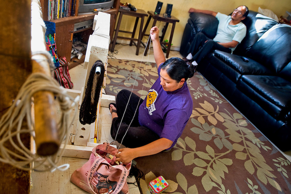 050510       Brian Leddy.Pamela Brown weaves a rug in her living room while her father Gilbert Farley watches television at their home near Sanostee on Friday. Brown, who has been weaving since she was about six, sold a rug to the Toadlena Trading Post that marked the store's 5000th rug purchased.
