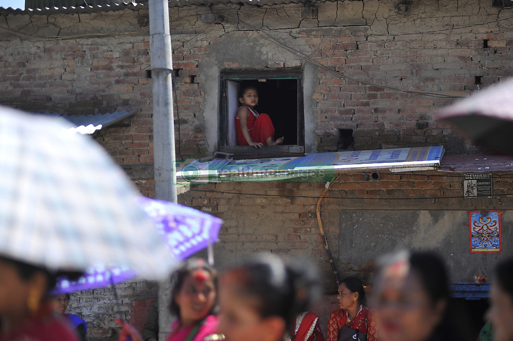 August 26, 2017 - Kathmandu, NP, Nepal - A Little girl glancing from window as Nepalese Hindu devotees lining to offer prayer at the Rishishwor Mahadev Temple during Rishi Panchami Festival celebrations at Teku, Katmandu, Nepal on Saturday, August 26, 2017. Rishi Panchami festival is celebrated as the last day of three-day long Teej Festival. The Teej festival is celebrated by Hindu women in Nepal as well as in some parts of India.  During the three-day long festival, women observe a day-long fast and pray for the long life their husbands as well as for a happy family. Those who are unmarried pray for a good husband and a long life. (Credit Image: © Narayan Maharjan/Pacific Press via ZUMA Wire)