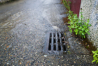Water flowing down a street to a storm drain on a rainy day.
