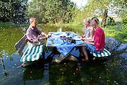 """ELbe floods in Gorleben. Die Familie des Elbefischers Christian Köthke (links) in Gorleben lässt sich vom """"Jahrhunderthochwasser 2002"""" nicht aus der Ruhe bringen. Sie lud zur Kaffeerunde in ihren überschwemmten Garten direkt am Ufer der Elbe."""