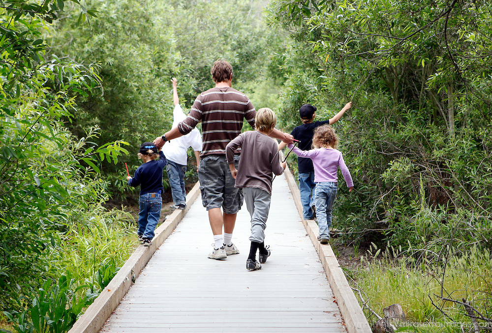 USA, California, San Diego. A father walks with his kids on a nature trail at San Elijo Lagoon.