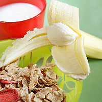 An healthy breakfast, milk, cereals and banana, on green background