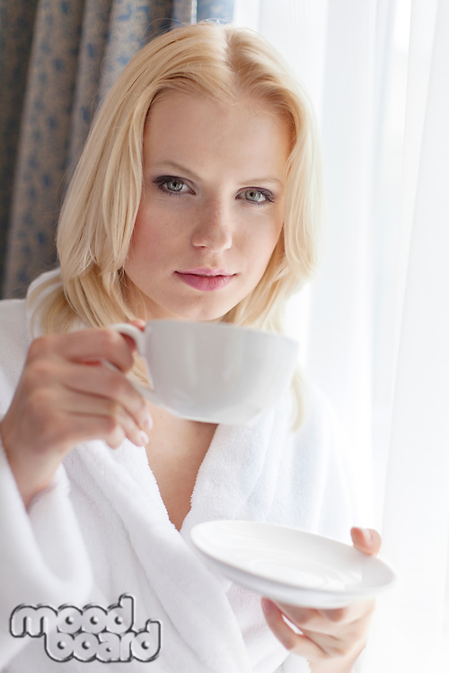 Portrait of attractive young woman in bathrobe drinking coffee at hotel room
