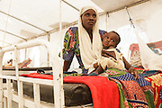 A woman holds her child, who is recovering from malnutrition, as she sits on a bed in a tent at a UNICEF-sponsored therapeutic feeding center at the Mongo hospital in the town of Mongo, Guera province, Chad on Tuesday October 16, 2012.