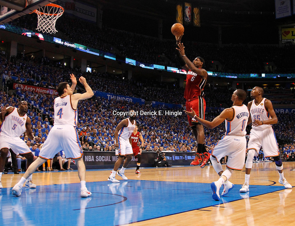 Jun 12, 2012; Oklahoma City, OK, USA;  Miami Heat small forward LeBron James (6) lays the ball up past Oklahoma City Thunder point guard Russell Westbrook (0), Kevin Durant (35) and Nick Collison (4) during the first quarter of game one in the 2012 NBA Finals at the Chesapeake Energy Arena.  Mandatory Credit: Derick E. Hingle-US PRESSWIRE