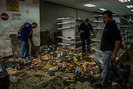 CARACAS, VENEZUELA - APRIL 21, 2017: Staff work to clean the Ofercenter supermarket that was one of over a dozen stores looted late at night in El Valle, a working class neighborhood in Caracas. The streets of Caracas erupted into a night of riots, looting and clashes with National Guardsmen as anger from two days of pro-democracy protests spilled into unrest in working class neighborhoods and slums. Shots rang out throughout the night in El Valle, a neighborhood of mixed loyalties, as armored vehicles struggled to contain crowds of looters. At one point during the night, clashes became so heavy that a nearby children's hospital was evacuated after the ward filled with tear gas.