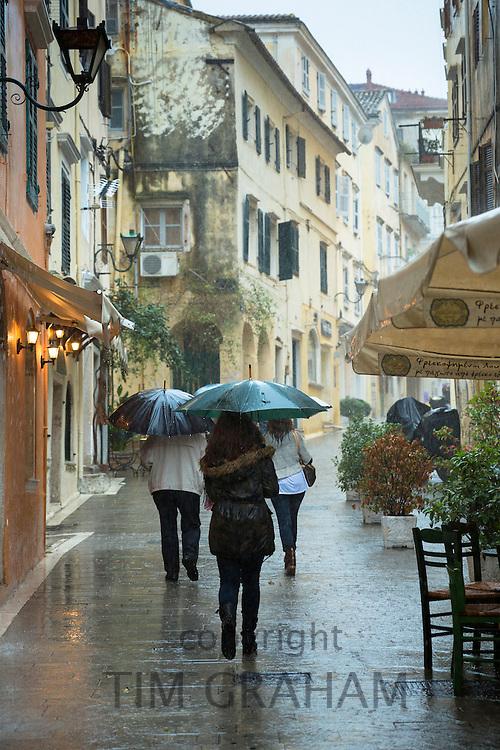 People walking with umbrella in rainy day scene in Kerkyra, Corfu Town, Greece