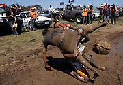 """A couple of festival-goers wrestle in a pool of mud at the annual Deniliquin Ute Muster in Deniliquin, Australia. A """"ute"""" is a term used in Australia for a utility vehicle, popular in the rural areas and used for farming and other work needs."""