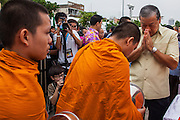 13 APRIL 2013 - BANGKOK, THAILAND: Bangkok Governor SUKHUMBHAND PARIBATRA makes merit by giving alms to monks in front of the Bangkok City Hall building on Songkran. Songkran is the traditional Thai New Year's Festival. It is held April 13-16. Many Thais mark the holiday by going to temples and making merit by giving extra alms to monks or offering extra prayers. They also mark Songkran with joyous water fights. Songkran has been a national holiday since 1940, when Thailand moved the first day of the year to January 1.    PHOTO BY JACK KURTZ