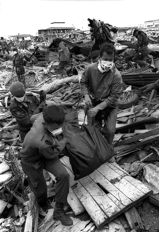 Body collectors climb of the Tsunami affected wreckage that was Banda Aceh. Indonesia.