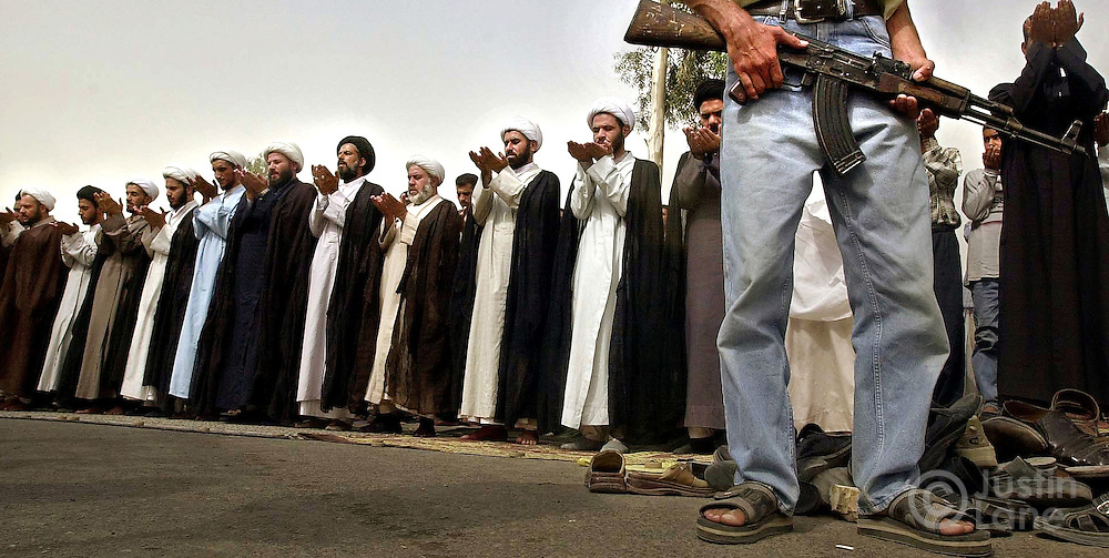 Iraqi men pray outside of a mosque in Baghdad under the watchful eye of an armed guard.