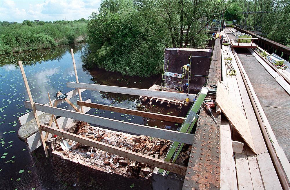 Nederland,Den Bosch , 20030605. .De Moerputtenbrug van het voormalige Halve Zolenlijntje bij Den Bosch wordt de komende jaren gerestaureerd. .Bouwvakkers zijn bezig steigers vast te maken aan de pijlers ivm. de restauratie. Op de voorgrond een pijler waar al een deel van de stenen zijn losgehakt. Boomwortels zitten tot een halve meter in het metselwerk..1 November 2005 zal een wandelroute over de voormalige spoorbrug worden geopend..Omdat de brug midden in het Natuurgebied de Moerputten ligt zullen de brugdelen op een andere plek worden gerestaureerd...Netherlands, Den Bosch, 20030605. .The Moerputten Bridge in Den Bosch iwill be restored in the coming years. 1 November 2005, a hiking trail on the former railway bridge opened. The bridge is in the middle of the nature reserve.