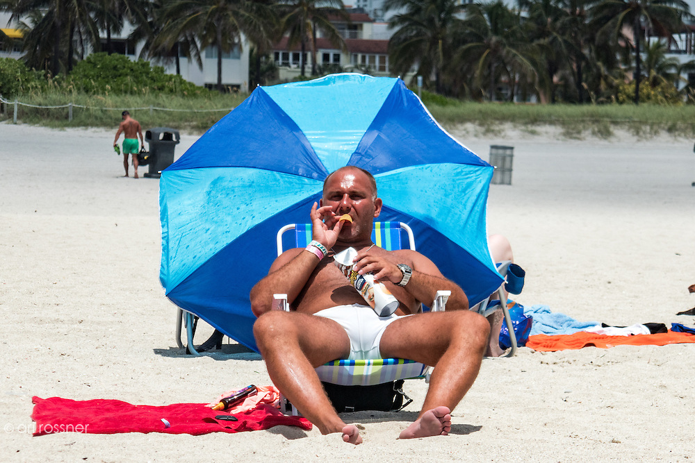 Man sunbathing on the beach while eating springles