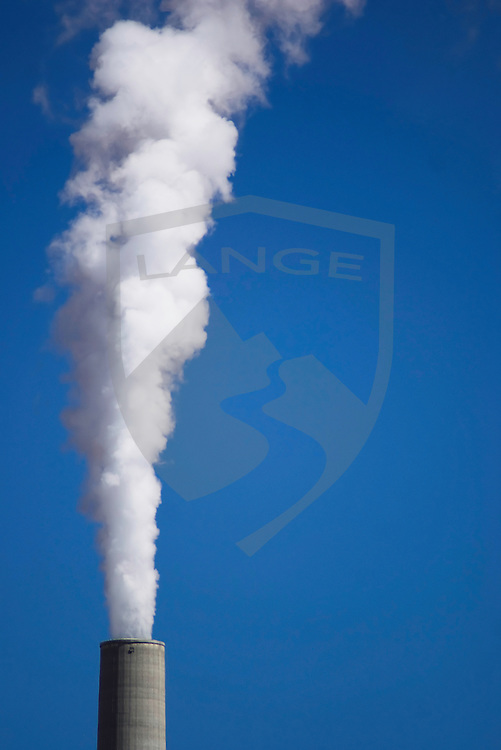 environment and nature: smoke stacks with white smoke and blue sky at the navajo coal burning power plant, page, arizona, usa
