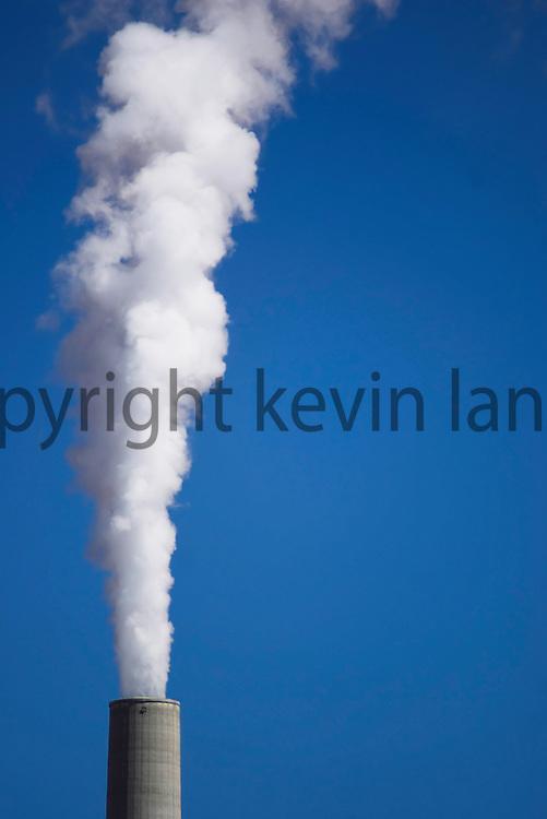 environment and nature: smoke stacks with white smoke and blue sky at the navajo coal burning power plant, page, arizona, usa