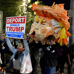 Protesters carry a paper bust of Donald Trump during a Anti-Donald Trump protest in front of City Hall on Wednesday, Nov. 9, 2016 in Los Angeles. Donald Trump has been elected as the next president of the United States.