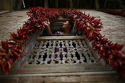 August 18, 2017 - Lalitpur, Nepal - A woman reacts as she looks out a window with hung red chilies at a house in the outskirts of Kathmandu, Nepal on Friday, August 18, 2017. (Credit Image: © Skanda Gautam via ZUMA Wire)