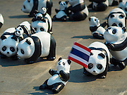 "04 MARCH 2016 - BANGKOK, THAILAND: Some of the 1600 paper maché pandas in the ""1600 Pandas+ World Tour in Thailand: For the World We Live In and the Ones We Love"" exhibit on Sanam Luang in Bangkok hold a Thai flag. The 1600 paper maché pandas, an art installation by French artist Paulo Grangeon will travel across Bangkok and parts of central Thailand for the next week and then will be displayed at Central Embassy, a Bangkok shopping mall, until April 10. The display of pandas in Thailand is benefitting World Wide Fund for Nature - Thailand and is sponsored by Central Embassy with assistance from the Tourism Authority of Thailand and Bangkok Metropolitan Administration and curated by AllRightsReserved Ltd.     PHOTO BY JACK KURTZ"