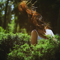 outdoors portrait of a girl among trees and foliage