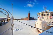 Fartyg i is och med snö på Riddarfjärden med Stadshuset på Kungsholmen i Stockholm