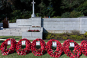 The Cross of Sacrifice with wreaths of poppies during the Remembrance Sunday ceremony at the Hodogaya, Commonwealth War Graves Cemetery in Hodogaya, Yokohama, Kanagawa, Japan. Sunday November 11th 2018. The Hodagaya Cemetery holds the remains of more than 1500 servicemen and women, from the Commonwealth but also from Holland and the United States, who died as prisoners of war or during the Allied occupation of Japan. Each year officials from the British and Commonwealth embassies, the British Legion and the British Chamber of Commerce honour the dead at a ceremony in this beautiful cemetery. The year 2018 marks the centenary of the end of the First World War in 1918.