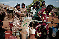 People displaced by the war between the government of Sri Lanka and the LTTE pump water in a camp for internally displaced people at the Menick farm near Vavuniya, Sri Lanka on July 8, 2009. Nearly 300,000 people remain in camps after the war as the government works on resettling them and screening for remaining LTTE members.