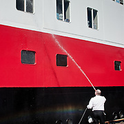 Three weeks aboard the Kong Harald. Hurtigruten, the Coastal Express. Man cleaning the ship.