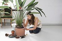 Woman potting plant on floor in home