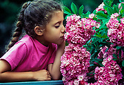 Girl sniffing flowers.