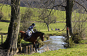 Young woman rides a Cleveland Bay cross Thoroughbred horse  in  cross-country eventing competition, Gloucestershire, UK
