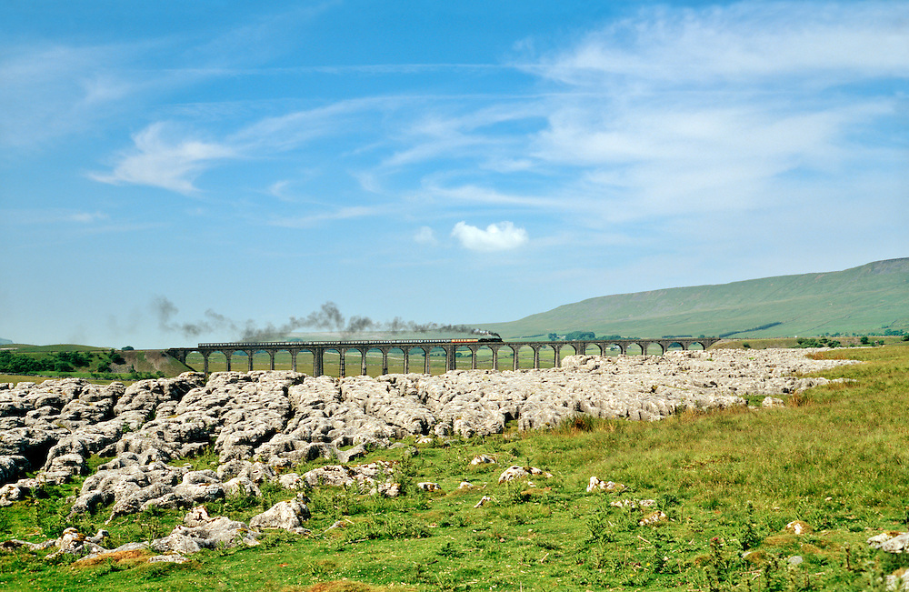 Steam railway engine train crosses the Ribblehead Viaduct in the limestone landscape of Yorkshire Dales National Park, England