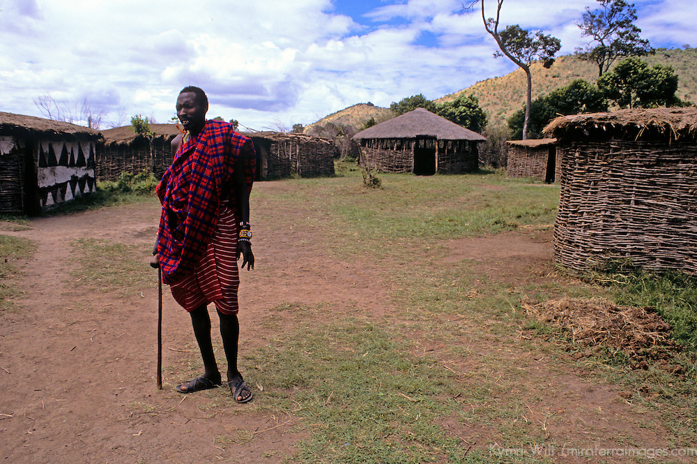 Africa, Kenya, Maasai Mara. A tall Maasai elder stands at the entrance to the boma at Olanana in the Maasai Mara.