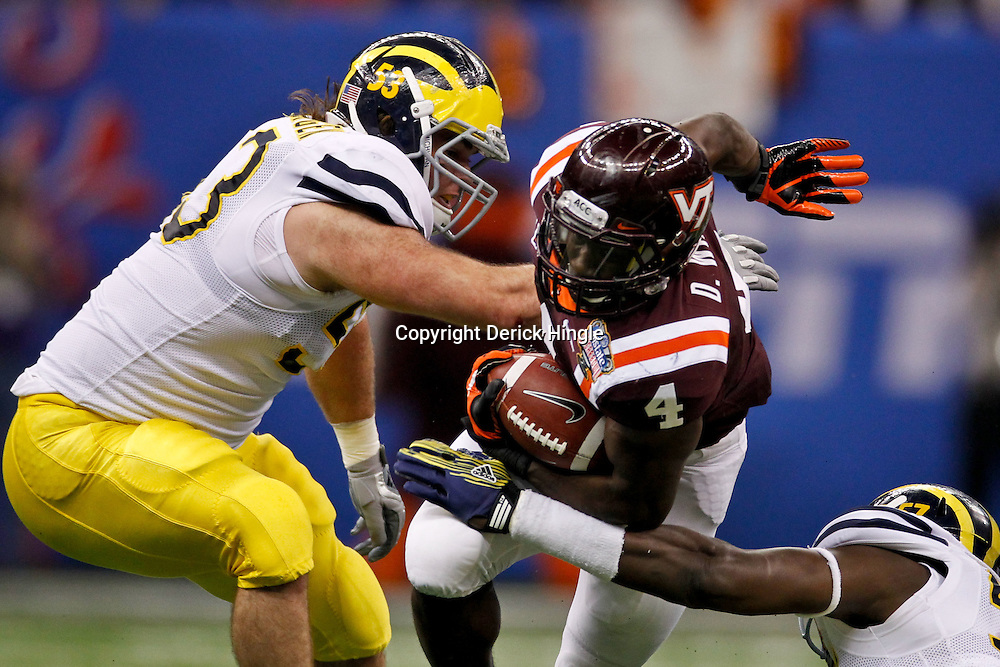 January 3, 2012; New Orleans, LA, USA; Virginia Tech Hokies running back David Wilson (4) runs between Michigan Wolverines defensive end Frank Clark (57) and defensive end Ryan Van Bergen (53) during the first quarter of the Sugar Bowl at the Mercedes-Benz Superdome.  Mandatory Credit: Derick E. Hingle-US PRESSWIRE
