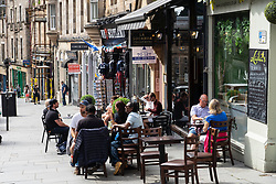 Edinburgh, Scotland, UK. 12 July, 2020, Business slowly returning to normal in Edinburgh city centre. Tourists still almost non existent and streets remain very quiet in the Old Town.Outdoor seating at bistro on Cockburn Street is popular.Iain Masterton/Alamy Live News