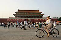 Eine Radfahrerin faehrt am Tiananmen Tor vorbei. © Urs Bucher/EQ Images