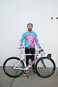 A fixed gear track cyclist poses for a portrait before The Red Hook Crit, a fixed gear criterium cycling race in Red Hook, Brooklyn, New York.