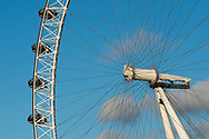 Low angle view of four passenger capsules suspended from London Eye, also known as the Millennium Wheel, against a blue sky in London, England.